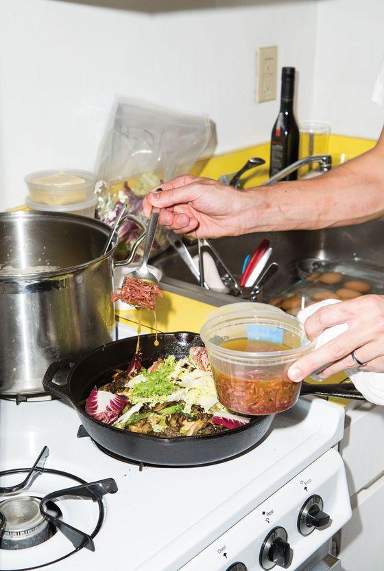 Saffer spooning soppressata sauce over the wild mushrooms and chicory.