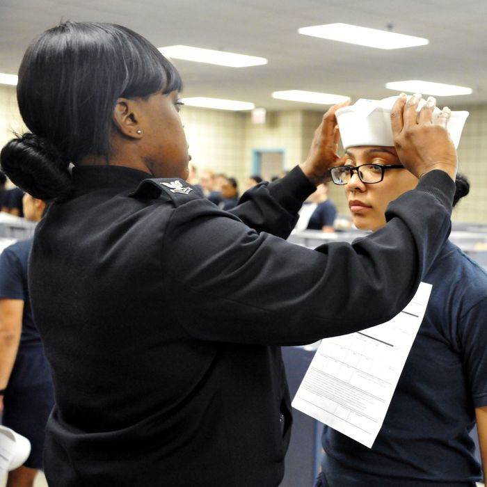 Engineman 2nd Class Shanice Floyd, a recruit division commander, ensures the proper fit of Seaman Recruit Megan Marte's white enlisted hat, or