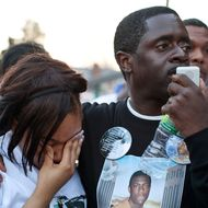 NEW YORK, NY - MARCH 22:  Jazzminn Mack (L), girlfriend of Ramarley Graham, cries while Franclot Graham, father of Ramarley Graham, speaks during a vigil for his son outside New York City Police Department's 47th Precinct on March 22, 2012 in the Bronx borough New York City. Graham, 18, was shot in the chest by police officers in his grandmother's bathroom after the officers entered the house without a warrent. Graham, was unarmed; he was attempting to flush a bag of marijuana down the toilet.  (Photo by Andrew Burton/Getty Images)
