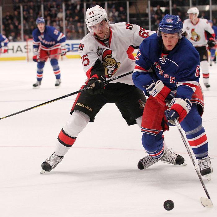 Carl Hagelin #62 of the New York Rangers skates with the puck against Erik Karlsson #65 of the Ottawa Senators