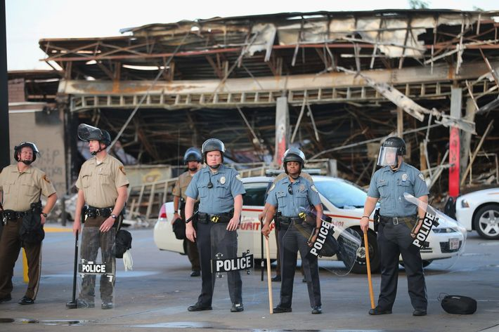 FERGUSON, MO - AUGUST 11: Police guard a Quick Trip gas station that was burned yesterday when protests over the killing of 18-year-old Michael Brown turned to riots and looting on August 11, 2014 in Ferguson, Missouri. Police responded with tear gas and rubber bullets as residents and their supporters protested the shooting by police of an unarmed black teenager named Michael Brown who was killed Saturday in this suburban St. Louis community. Yesterday 32 arrests were made after protests turned into rioting and looting in Ferguson.  (Photo by Scott Olson/Getty Images)