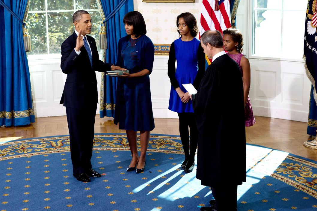 U.S President Barack Obama (L) takes the oath of office from U.S. Supreme Court Chief Justice John Roberts (R) as first lady Michelle Obama (2nd L) holds the bible and daughter Malia (C) and Sasha looks on in the Blue Room of the White House  January 20, 2013 in Washington, DC. Obama and U.S. Vice President Joe Biden were officially sworn in a day before the ceremonial inaugural swearing-in.