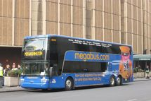 Coach USA Megabus.com Van Hool TD925 Astromega double-deck bus DD415 waits outside Madison Square Garden and Penn Station.