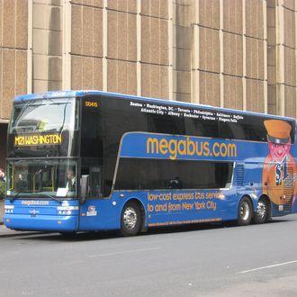 Coach USA Megabus.com Van Hool TD925 Astromega double-deck bus DD415 waits outside Madison Square Garden and Penn Station.