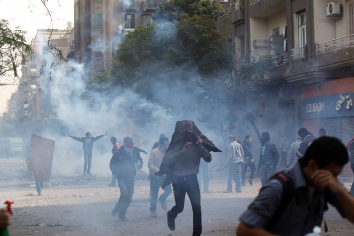 Egyptians protesters run for cover to escape tear gas fired by riot police during clashes at Cairo's landmark Tahrir Square on November 20, 2011. Several hundred Egyptians occupied Cairo's Tahrir Square with sporadic clashes between protesters and the police following a night of deadly violence, an AFP correspondent said.  AFP PHOTO / KHALED DESOUKI (Photo credit should read KHALED DESOUKI/AFP/Getty Images)