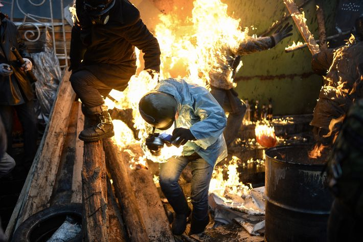 "Protesters catch fire as they stand behind burning barricades during clashes with police on February 20, 2014 in Kiev. Ukraine's embattled leader announced a ""truce"" with the opposition as he prepared to get grilled by visiting EU diplomats over clashes that killed 26 and left the government facing diplomatic isolation. The shocking scale of the violence three months into the crisis brought expressions of grave concern from the West and condemnation of an ""attempted coup"" by the Kremlin. AFP PHOTO/BULENT KILIC        (Photo credit should read BULENT KILIC/AFP/Getty Images)"