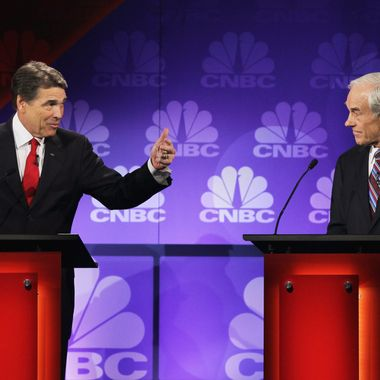 ROCHESTER, MI - NOVEMBER 09: Texas Gov. Rick Perry (L) speaks as U.S. Rep. Ron Paul (R-TX) looks on during a debate hosted by CNBC and the Michigan Republican Party at Oakland University on November 9, 2011 in Rochester, Michigan. The debate is the first meeting of the eight GOP presidential hopefuls since allegations of sexual impropriety have surfaced against front-runner Herman Cain.   (Photo by Scott Olson/Getty Images)