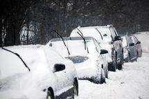 Cars lie buried under snow