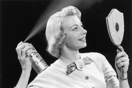 circa 1955:  A woman applies hair spray while looking into a handheld mirror.  (Photo by Lambert/Getty Images)