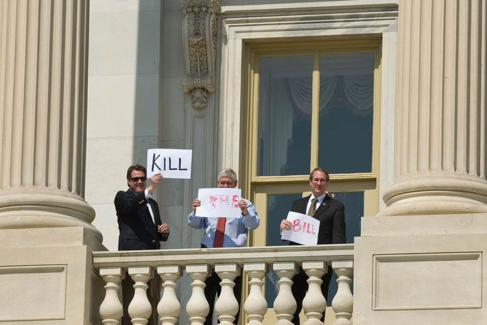 """House Republicans (LtoR) Michael Turner, R-OH., Pete Sessions, R-TX., and Bob Goodlatte, R-VA., hold up """"Kill the Bill"""" signs form the balcony of the Capitol to dozens of protesters as the House prepares for the vote on healthcare reform on Sunday, March 21, 2010."""