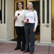 Erika Turner (R) and Jennifer Melsop (2nd R) of Centreville, Virginia, becomes the first same sex marriage in Arlington County as the couple come out from Arlington County Courthouse as Clerk of the Circuit Court of Arlington County Paul Ferguson (L) looks on October 6, 2014 in Arlington, Virginia.