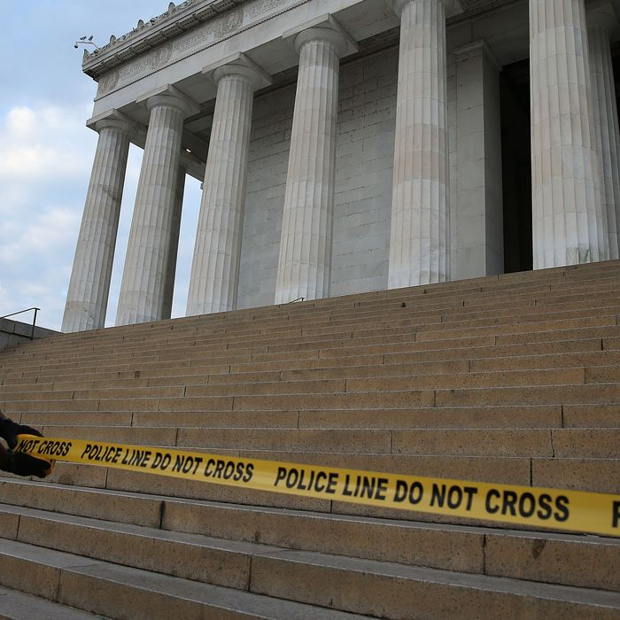 WASHINGTON, DC - OCTOBER 01: A U.S. Park Police officer uses police tape to close the Lincoln Memorial, October 1, 2013 in Washington, DC. The National Mall and all monuments and large sections of the government will close due to government shut down after Congress failed to agree on spending. (Photo by Mark Wilson/Getty Images)