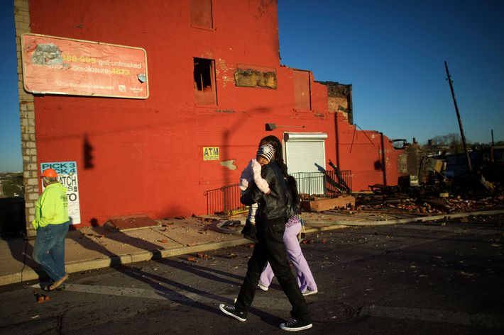 BALTIMORE, MD - APRIL 28:  A man carries a young child past the remains of convenience store and a senior center set ablaze during night riots smolder at dawn on April 28, 2015 in Baltimore, Maryland. A state of emergency has been declared in Baltimore following violent protests which erupted after the funeral service for Freddie Gray. Gray, 25, was arrested for possessing a switch blade knife on April 12 outside the Gilmor Homes housing project on Baltimore's west side and according to his attorney died a week later in the hospital from a severe spinal cord injury he received while in police custody. (Photo by Mark Makela/Getty Images)