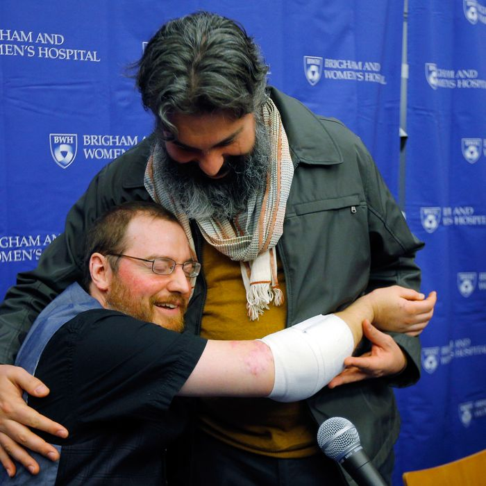 Will Lautzenheiser (L) hugs his partner Angel Gonzalez at a news conference to announce Lautzenheiser's successful double arm transplant at Brigham and Women's Hospital in Boston, Massachusetts November 25, 2014. Lautzenheiser, a 40-year-old quadruple amputee, on Tuesday thanked the Boston surgeons who performed a rare dual arm transplant on him last month and described the experience of getting the new limbs as surreal. Lautzenheiser, who lost his arms and legs to a streptococcal infection in 2011, said he has limited function in the new arms, which are encumbered by wrappings to help with healing.