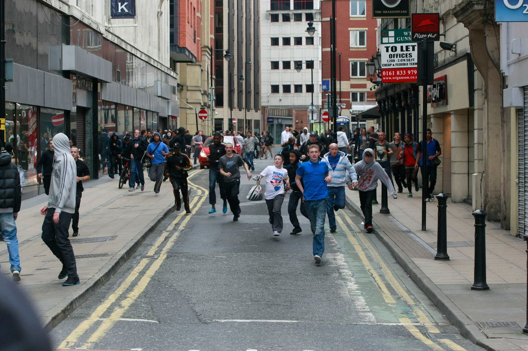 MANCHESTER, UNITED KINGDOM - AUGUST 09: People run down Market Street in Manchester City Centre on August 9, 2011 in Manchester, England. After three nights of rioting and looting in and around London, the chaos is starting to spread to other cities around Britain.  (Photo by Nathan Cox/Getty Images)