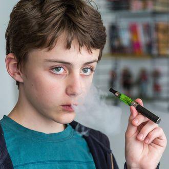 Teenager smoking electronic cigarette.