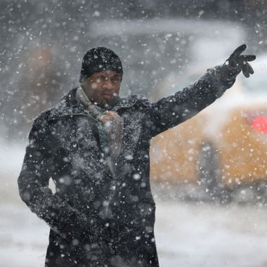 NEW YORK, NY - FEBRUARY 13:  A man hails a taxi in the snow on February 13, 2014 in New York City. Heavy snow and high winds made for a hard morning commute in the city.  (Photo by John Moore/Getty Images)