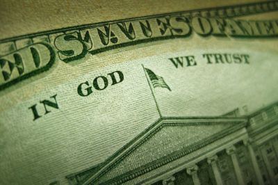 """A macro close up photo emphasizing the inscription """"In God We Trust"""" printed on the back of an United States ten dollar bill with selective focus on the work God."""