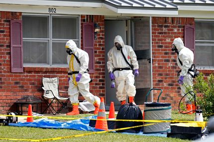 Federal agents wearing hazardous material suits and breathing apparatus exit the home and possessions in the West Hills Subdivision house of Paul Kevin Curtis in Corinth, Miss., Friday, April 19, 2013. Curtis is in custody under the suspicion of sending letters covered in ricin to the U.S. President Barack Obama and U.S. Sen. Roger Wicker, R-Miss. (AP Photo/Rogelio V. Solis)
