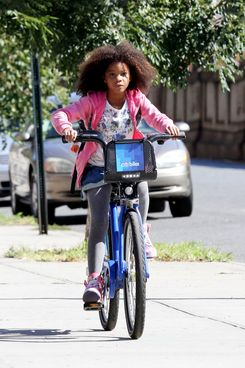 Quvenzhane Wallis rides a public bike while shooting the remake of 'Annie', on location in Harlem, NY.