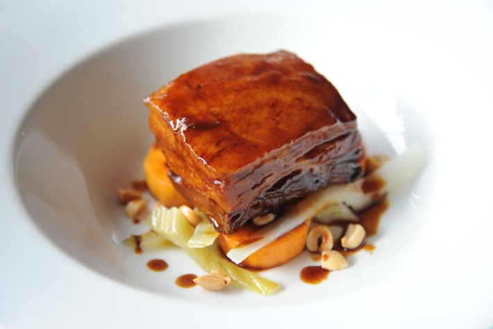 Noreetuh's pineapple-braised pork belly, yams, mustard greens, and peanuts.