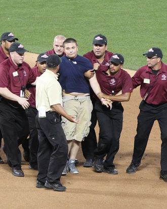 16 July 2013: A young fan runs onto the field and is captured by security and escorted away during the 2013 MLB All-Star Game between the American League and National League teams at Citi Field in Flushing, NY.