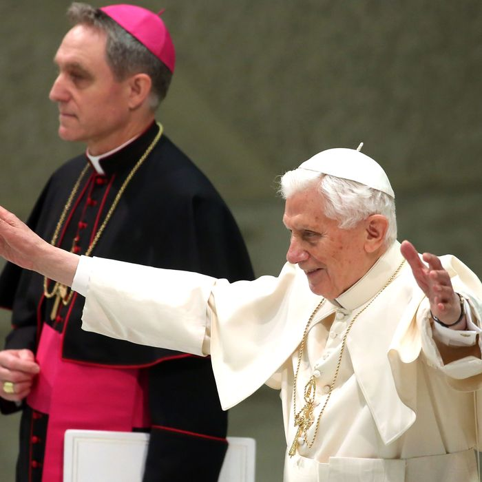 Pope Benedict XVI, anked by his personal secretary Georg Ganswein (L), waves to the faithful as he arrives at the Paul VI Hall for his weekly audience on February 13, 2013 in Vatican City, Vatican. The Pontiff will hold his last weekly public audience on February 27 at St Peter's Square after announcing his resignation earlier this week.