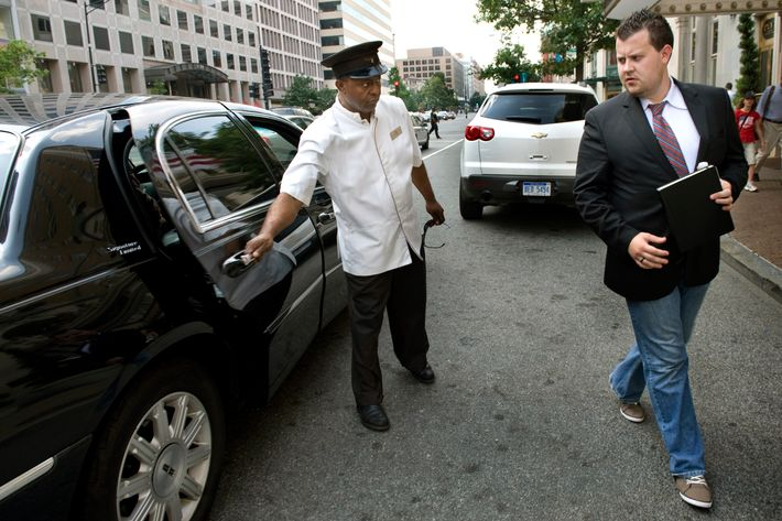 WASHINGTON, DC  - JULY 16: (L-R) Hotel employee Tedros Birat opens the Uber Car door for Brendan Kownacki who uses the UBER car via a smartphone app to get around town rather than cabs in Washington, DC on July 16, 2012.  He pays a little more than cabs but says it's worth it.  It's automatically billed to his credit card, tip included, and the quality of the cars and drivers leaves no surprises for him or his clients.  (Photo by Linda Davidson / The Washington Post)
