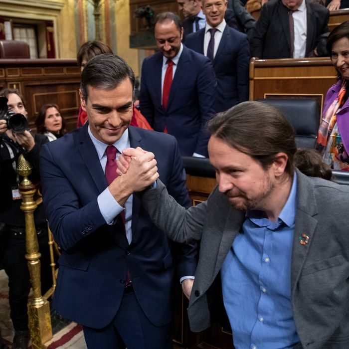 Spain's interim Prime Minister Pedro Sánchez (L) and Unidas Podemos party leader Pablo Iglesias (R) congratulate each other after learning the results of the vote on the last day of the investiture debate at the Spanish Parliament on January 07, 2020 in Madrid, Spain.