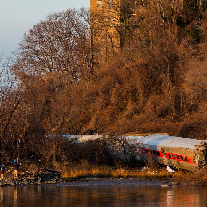 The wreckage of a Metro-North commuter train lies on its side after it derailed just north of the Spuyten Duyvil station December 1, 2013 in the Bronx borough of New York City. Multiple injuries and at least 4 deaths were reported after the seven car train left the tracks as it was heading to Grand Central Terminal along the Hudson River line.