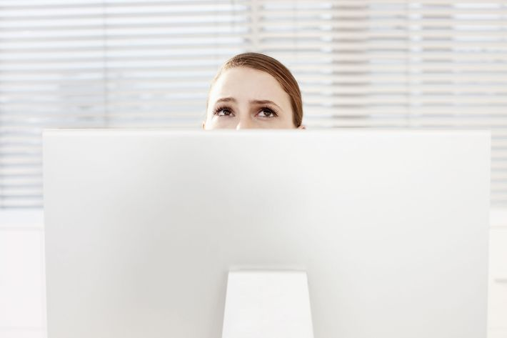 Businesswoman looking up behind computer monitor