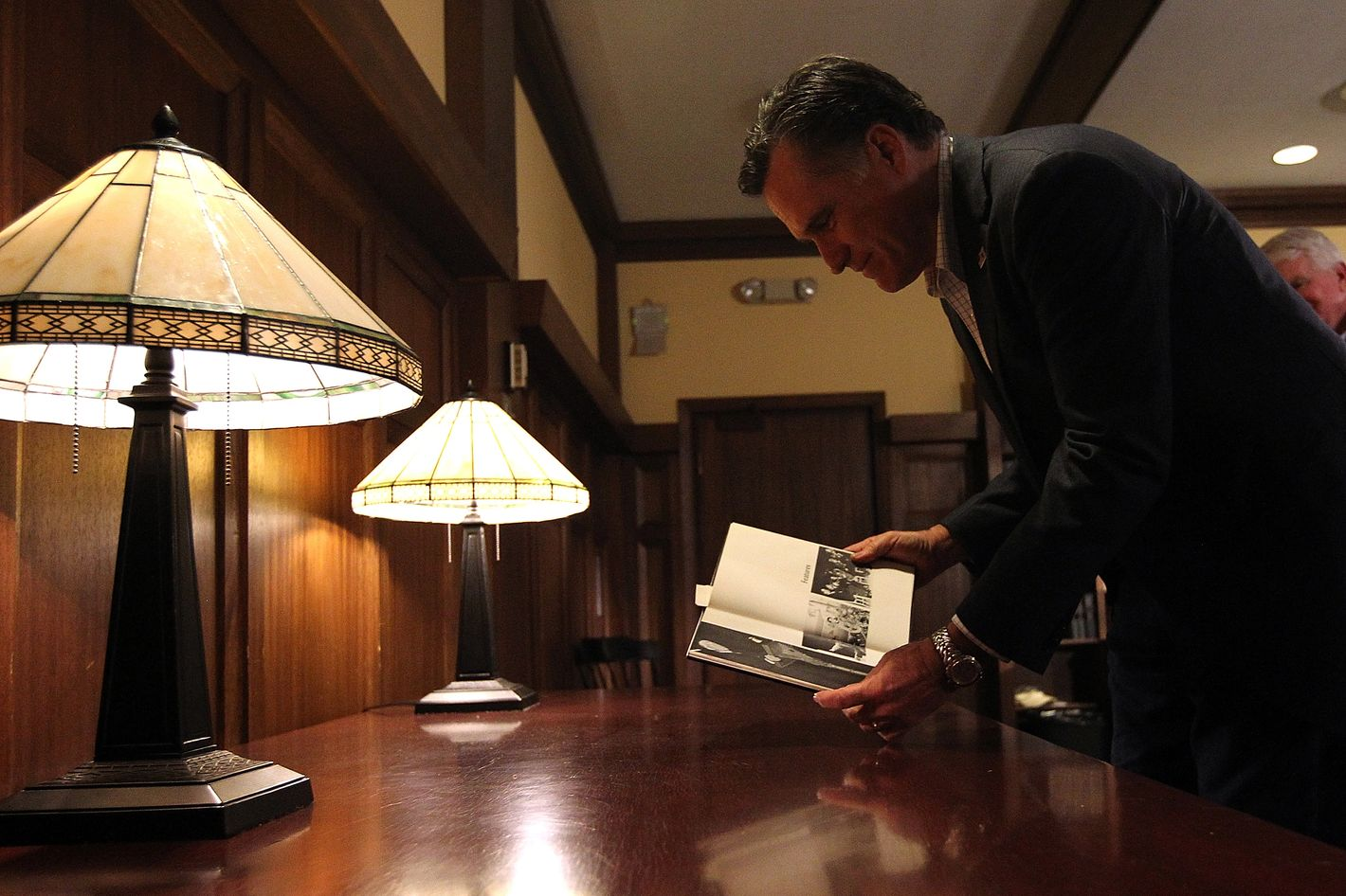 TILTON, NH - JANUARY 06:  Republican presidential candidate and former Massachusetts governor Mitt Romney looks at a copy of the 1968 Tilton School yearbook that features photos of his father when he was running for president before the start of a spaghetti dinner at Tilton School on January 6, 2012 in Tilton, New Hampshire. After spending a day campaigning in South Carolina, Mitt Romney returned to New Hampshire to make a final push ahead of the New Hampshire primary.  (Photo by Justin Sullivan/Getty Images)