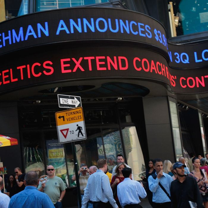 People walk under a ticker sign announcing Lehman Brothers financial losses September 10, 2008 in New York. Lehman Brothers plans to sell a majority stake in its investment management business and said a sale of the entire company was possible.