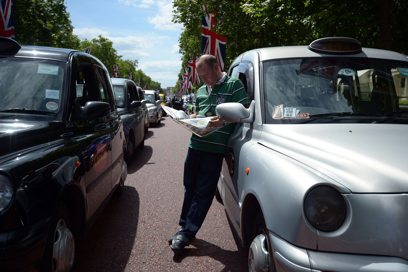 A London black cab driver reads a newspaper during a protest against a new private taxi service 'Uber', a mobile phone app, on the Mall leading to Buckingham Palace in central London on June 11, 2014. Taxi drivers brought parts of London, Paris and other European cities to a standstill on June 11 as they protested against new private cab apps such as Uber which have shaken up the industry. Thousands of London's iconic black cabs, many of them beeping their horns, filled the roads around Buckingham Palace, Trafalgar Square and the Houses of Parliament to the exclusion of any other vehicles. AFP PHOTO / CARL COURT