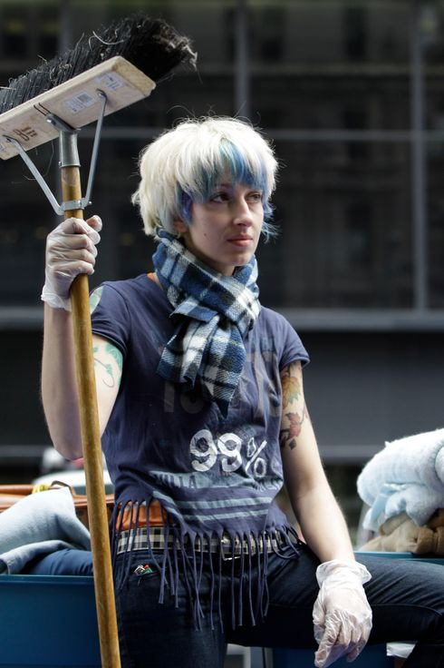 Lauren DiGioia poses with a broom for a photographer at Zuccotti Park in New York, Monday, Oct. 24, 2011.   Having started in New York, Occupy Wall Streets demonstrations now take place all across the United States, as protesters speak out against corporate greed and the gap between the rich and the poor. (AP Photo/Kathy Willens)