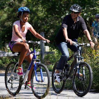 WEST TISBURY, MA - AUGUST 23: U.S. President Barack Obama (R) and daughter Malia Obama, 13, bike together on a bike path through Manuel F. Correllus State Forest while vacationing on Martha's Vineyard on August 23, 2011 in West Tisbury, Massachusetts. This is the third year the president has taken his vacation on Martha's Vineyard. (Photo by Matthew Healey-Pool/Getty Images)