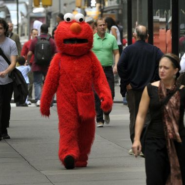 A person dressed as Elmo from the television show Sesame Street, walks to pose for pictures with tourists in Times Square October 4, 2012. GOP Presidential nominee Mitt Romney  mentioned Sesame Street  in Wednesday night's debate when he vowed to cut funding to public broadcasting if elected. PBS's Sesame Street will be celebrating its 43rd birthday this year. AFP PHOTO/ TIMOTHY A. CLARY        (Photo credit should read TIMOTHY A. CLARY/AFP/Getty Images)