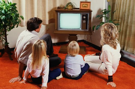 Family Seated on Living Room Floor Watching Television