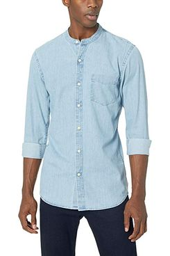 A male model wearing a men's slim-fit long-sleeve band collar light blue denim shirt from Goodthreads with a pair of dark wash jeans. The Strategist - A Bunch of Men's Button Downs (From $16) Are on Sale at Amazon.