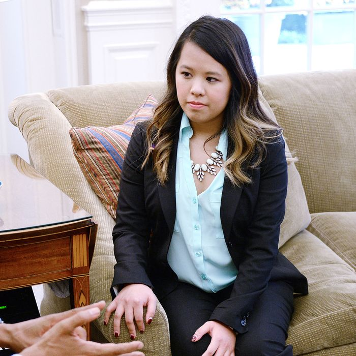 WASHINGTON, DC - OCTOBER 24: Dallas nurse Nina Pham listens to U.S. President Barack Obama in the Oval Office of the White House October 24, 2014 in Washington, DC. Pham, a nurse who was infected with Ebola from treating patient Thomas Eric Duncan at Texas Health Presbyterian Hospital in Dallas and was first diagnosed on October 12, was declared free of the virus on Friday. (Photo by Olivier Douliery-Pool/Getty Images)