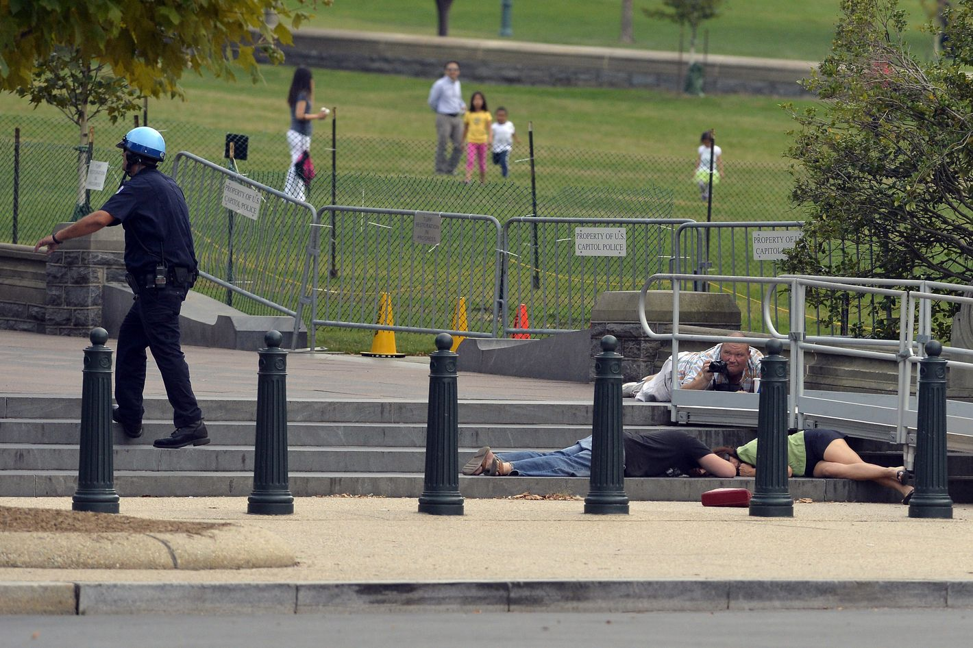 "People take cover as gun shots were being heard at the US Capitol in Washington, DC, on October 3, 2013. The US Capitol was placed on security lockdown Thursday after shots were fired outside the complex, senators said. ""Shots fired outside the Capitol. We are in temporary lock down,"" Senator Claire McCaskill said on Twitter. Police were seen running within the Capitol building and outside as vehicles swarmed to the scene."