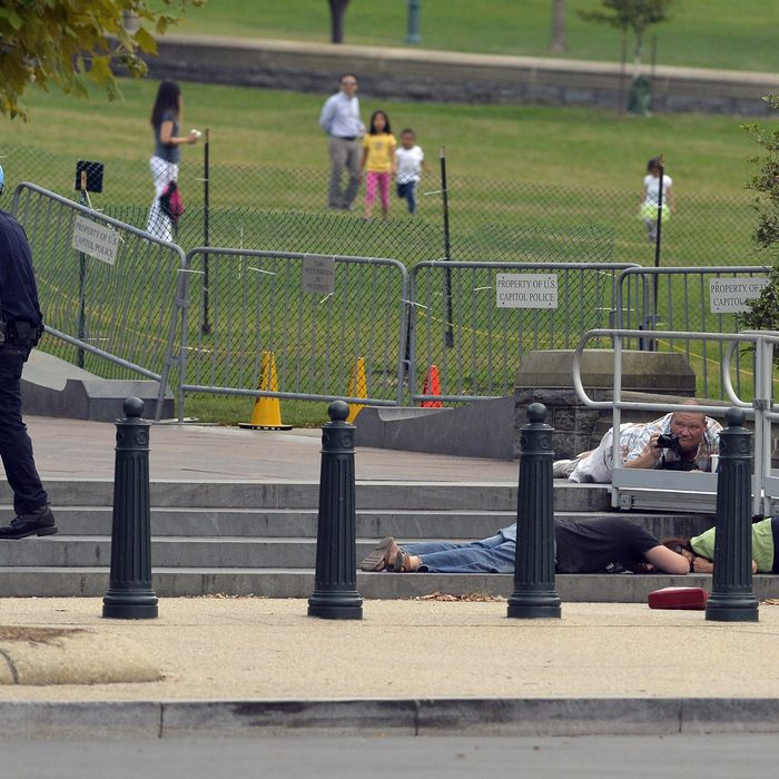 People take cover as gun shots were being heard at the US Capitol in Washington, DC, on October 3, 2013. The US Capitol was placed on security lockdown Thursday after shots were fired outside the complex, senators said.
