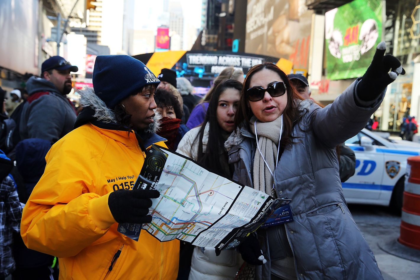 NEW YORK, NY - JANUARY 30:  Tourists ask for directions as football fans gather along Broadway in Times Square which has temporarily been re-named Super Bowl Boulevard as the city prepares for Sunday's game between the Denver Broncos and Seattle Seahawks on January 30, 2014 in New York City. Thousands of tourists have descended on Manhattan to soak up the pre game atmosphere which includes a toboggan ride, autograph booths and a penalty kick cage. Security is tight throughout the city with thousands of officers patrolling on foot and in vehicles.  (Photo by Spencer Platt/Getty Images)
