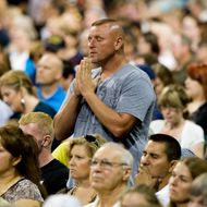 """HOUSTON, TX - AUGUST 6:  Gary Don Holley stands and prays amidst the crowd of participants during the non-denominational prayer and fasting event, entitled """"The Response"""" at Reliant Stadium August 6, 2011 in Houston, Texas. Thousands attended the event organized by Gov. Rick Perry in order to pray for God to help save """"a nation in crisis"""" referring to America.  (Photo by Brandon Thibodeaux/Getty Images)"""