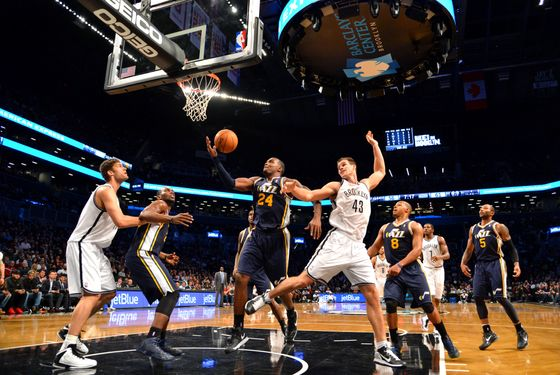Paul Millsap #24 of the Utah Jazz rebounds against Kris Humphries #43 of the Brooklyn Nets during the game at the Barclays Center on December 18, 2012  in Brooklyn, New York.