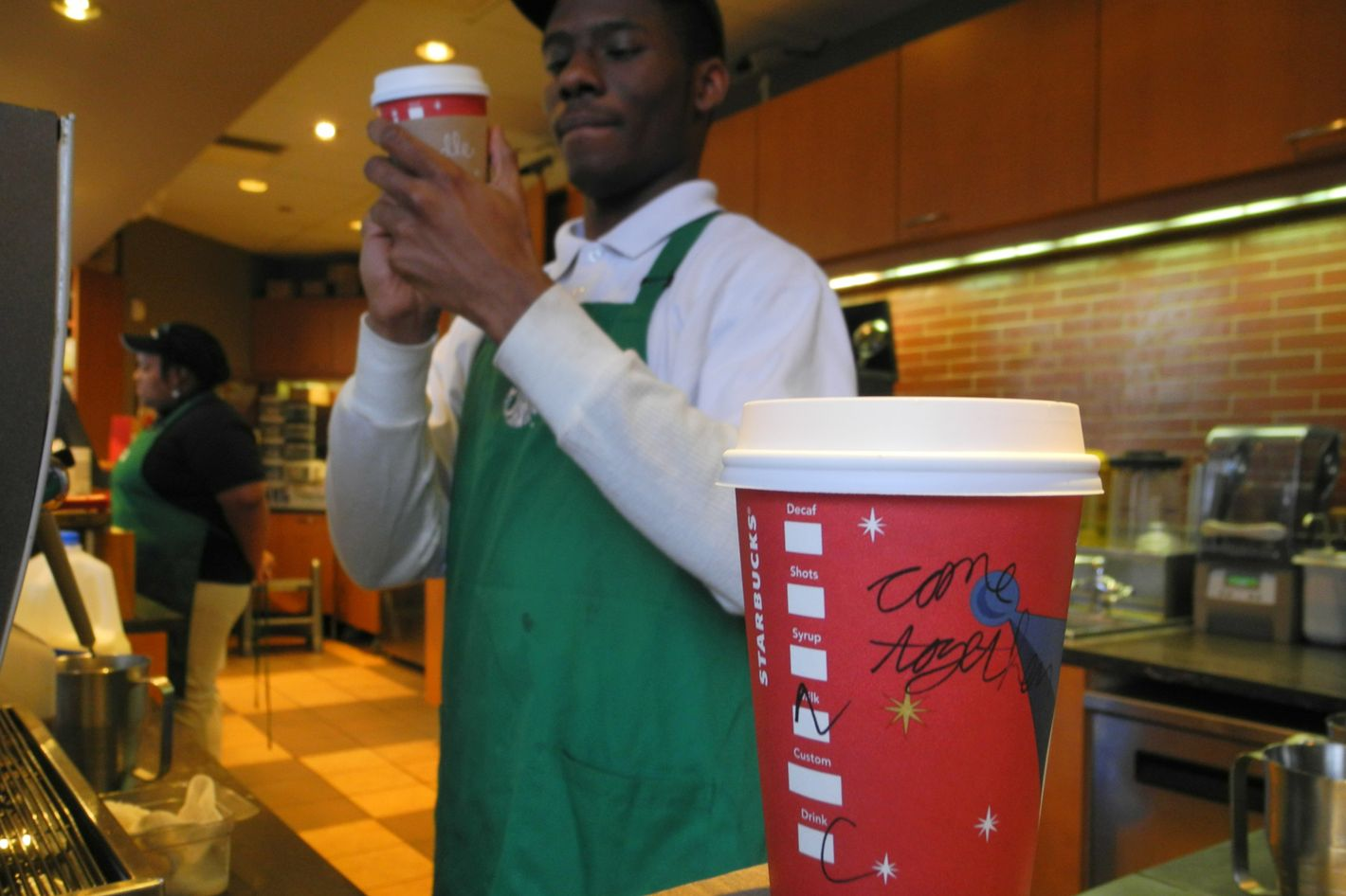 """A Starbucks employee writes a message on a cup of freshly brewed coffee at a local store in Washington, DC on December 26, 2012. Starbucks stirred the political pot Wednesday by urging its baristas to write """"come together"""" on its cups as a way to pressure US lawmakers to compromise on a deal to avert a year-end fiscal crisis. Starbucks chief executive Howard Schultz said the American coffee giant was recommending its first-ever message on the side of tall, grande and venti (small, medium and large) drinks sold at its Washington stores as a way to help break the capital's gridlock on the so-called """"fiscal cliff.""""  Lawmakers and the White House have less than a week to work out a deal aimed at preventing tax hikes from hitting all Americans and a series of deep, mandated spending cuts from kicking in beginning January 1."""