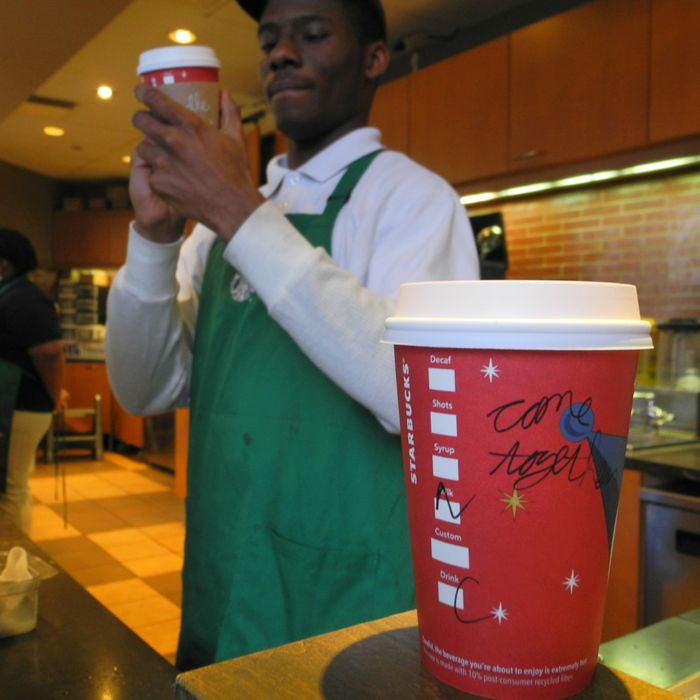 A Starbucks employee writes a message on a cup of freshly brewed coffee at a local store in Washington, DC on December 26, 2012. Starbucks stirred the political pot Wednesday by urging its baristas to write
