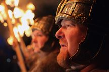 Men dressed as Vikings lead the torchlight procession