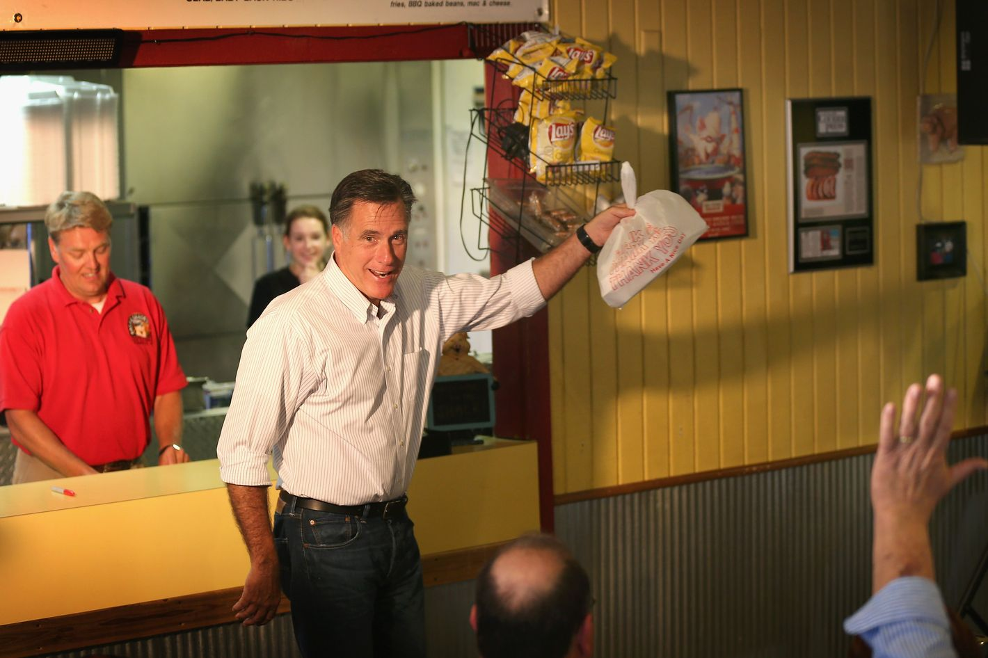 EVANSVILLE, IN - AUGUST 04:  Republican presidential candidate and former Massachusetts Gov. Mitt Romney (C) grabs a bag of food before leaving a campaign event at Stepto's Bar B Q Shack on August 4, 2012 in Evansville, Indiana. Romney told supporters gathered at the restaurant that the latest jobs report was evidence that Obama's economic policies were not working.  (Photo by Scott Olson/Getty Images)