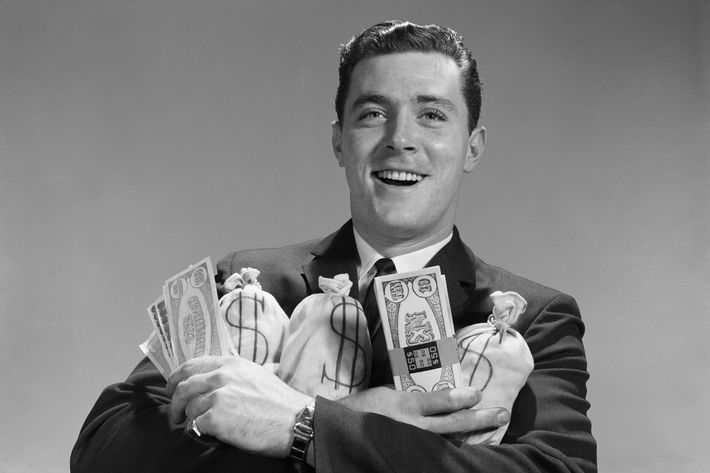 Smiling man holding money bags and bundles of cash